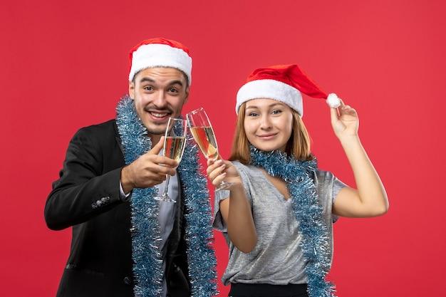 Вид спереди молодая пара празднует новый год на красной стене любовь рождественская вечеринка напиток
