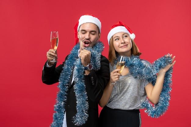 Giovani coppie di vista frontale che celebrano il nuovo anno sul natale rosso di amore di festa del pavimento