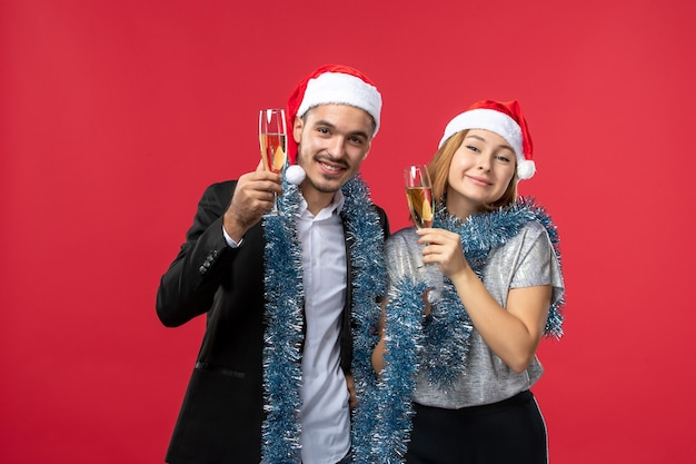 Front view young couple celebrating new year on red floor party love christmas