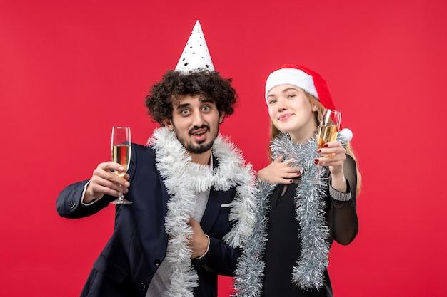Giovani coppie di vista frontale che celebrano il nuovo anno sulla festa rossa di amore di natale della parete