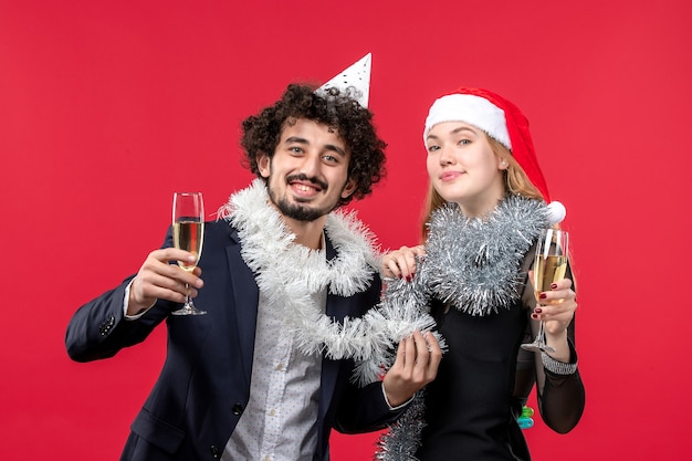 Giovani coppie di vista frontale che celebrano il nuovo anno sull'amore di natale di festa della parete rossa