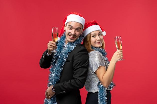 Le giovani coppie di vista frontale che celebrano il nuovo anno sulle feste rosse della parete amano il natale