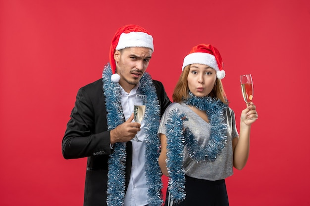 Front view young couple celebrating new year on a red wall party christmas love