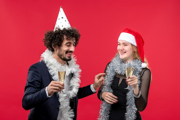 Front view young couple celebrating new year on a red wall party holiday christmas love