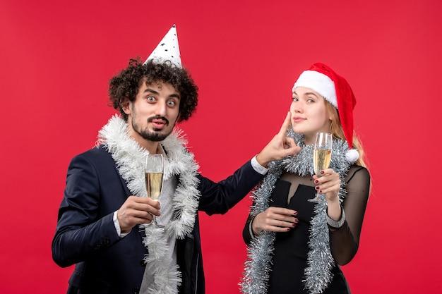 Giovani coppie di vista frontale che celebrano il nuovo anno sull'amore di natale di festa del partito della parete rossa