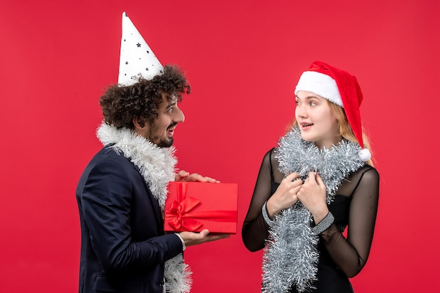 赤い壁の感情の愛のクリスマスに休日のプレゼントを交換する正面図の若いカップル