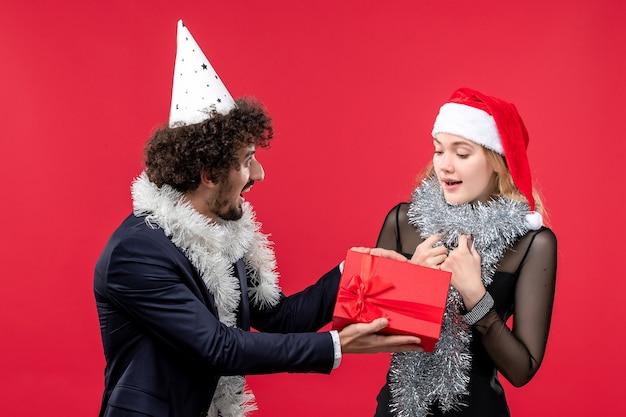 赤い壁の感情で休日のプレゼントを交換する正面図の若いカップルはクリスマスが大好きです