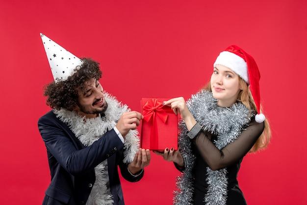 빨간색 바닥 감정 사랑 크리스마스에 새 해 선물을 들고 전면보기 젊은 부부