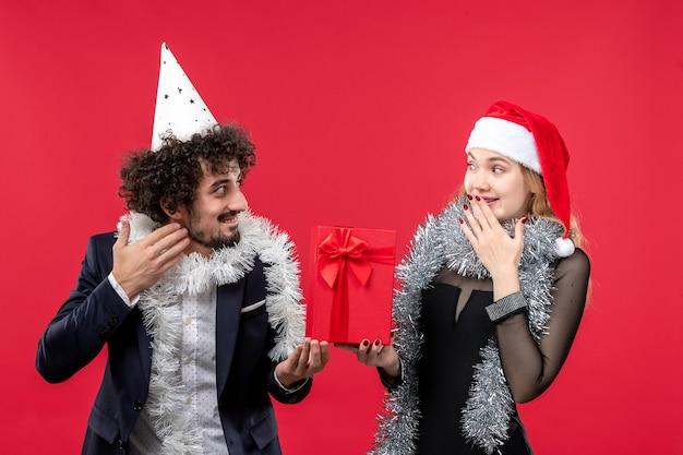 赤い壁の感情の愛のクリスマスに新年のプレゼントを保持している正面図若いカップル