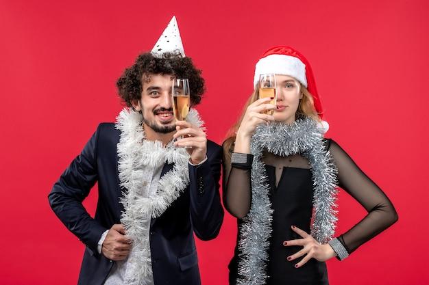 赤い壁のクリスマスの愛のパーティーでちょうど新年を祝う正面図の若いカップル