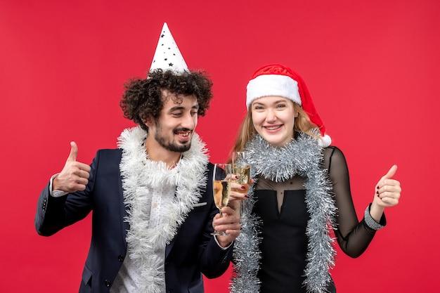 赤い壁のクリスマスの愛の写真で新年を祝うちょうど若いカップルの正面図