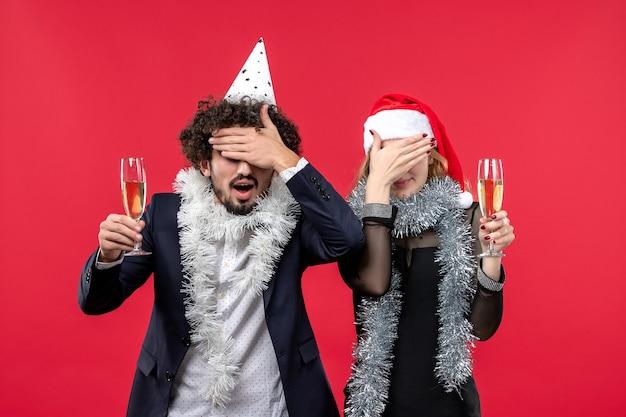 빨간 책상에 새해를 축하하는 전면보기 젊은 부부는 크리스마스 파티를 사랑합니다