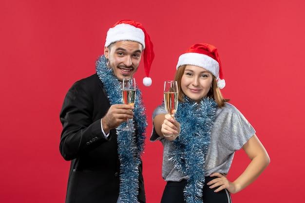 빨간 벽 크리스마스 사랑 파티에 새해를 축하 전면보기 젊은 부부