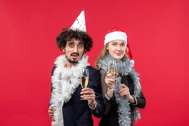 빨간 벽 색상 크리스마스 사랑 파티에 새해를 축하 전면보기 젊은 부부