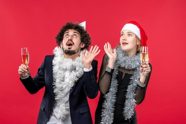빨간 벽에 새해를 축하하는 전면보기 젊은 부부는 크리스마스 파티 색상을 사랑합니다