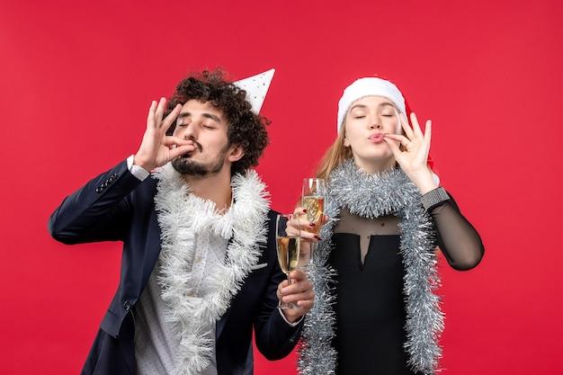 Giovani coppie di vista frontale che celebrano appena il nuovo anno sulla foto rossa di amore di natale dello scrittorio