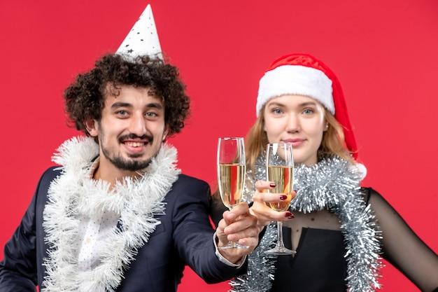 Giovani coppie di vista frontale che celebrano appena il nuovo anno sulla festa di amore di natale del pavimento rosso
