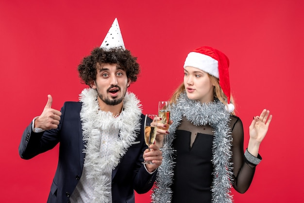 Front view young couple just celebrating new year on red wall christmas love photo