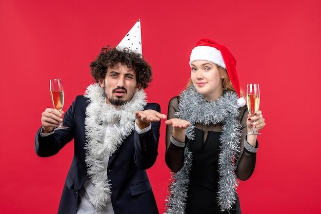 Giovani coppie di vista frontale che celebrano appena il nuovo anno su una festa di natale di amore della parete rossa