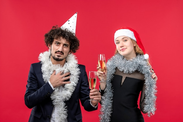 Front view young couple just celebrating new year on a red wall party christmas love
