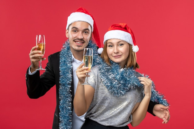 Front view young couple just celebrating new year on a red wall party love christmas