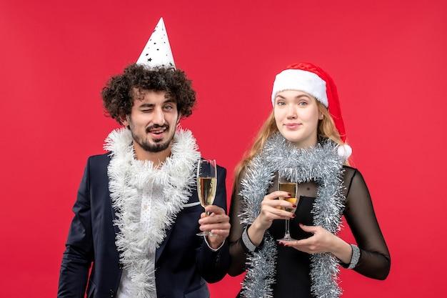 Giovani coppie di vista frontale che celebrano appena il nuovo anno sul colore rosso di amore di natale della foto della parete