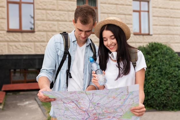 Молодая пара, глядя на карту, вид спереди
