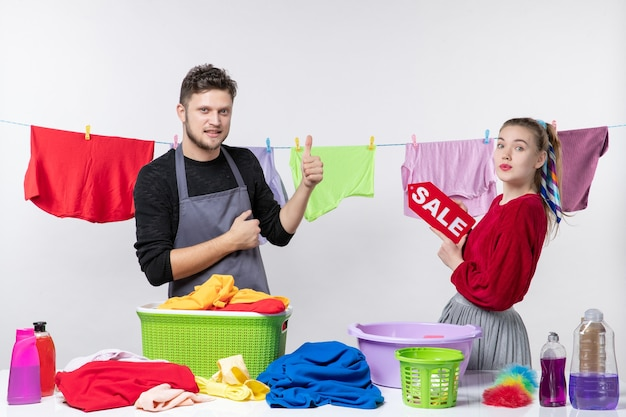 Vista frontale di una giovane coppia che dà i pollici in su e sua moglie che tiene in mano il segno di vendita vestiti sulla corda sul muro bianco