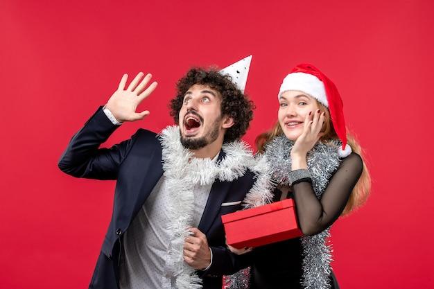 赤い壁の色のクリスマスの愛のパーティーに新年のプレゼントと正面図の若いカップル