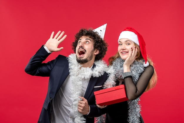 Front view young couple with new year present on red wall color christmas love party