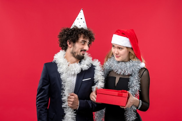 Front view young couple with new year present on the red wall party color christmas love