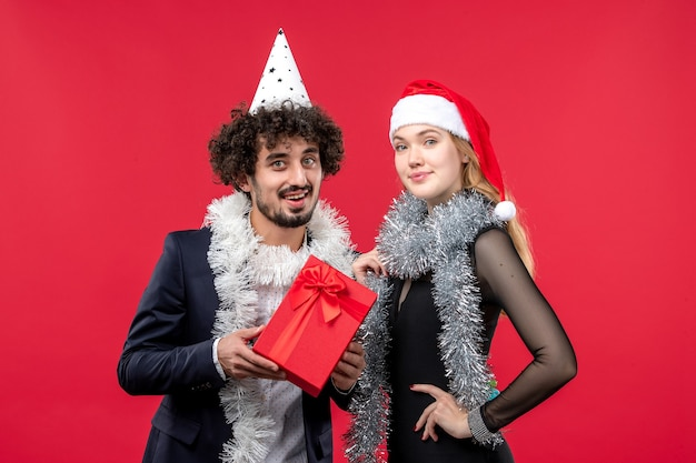 Вид спереди молодая пара с настоящим праздником на красной стене рождественской любовной вечеринки