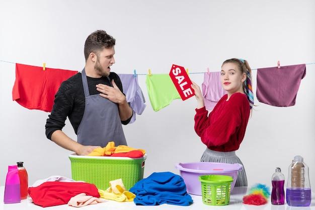 Vista frontale della giovane coppia donna con cartello di vendita e uomo confuso in piedi sul muro bianco