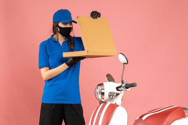 Vista frontale della giovane ragazza del corriere che indossa guanti con maschera medica in piedi accanto alla scatola di apertura della motocicletta su sfondo color pesca pastello