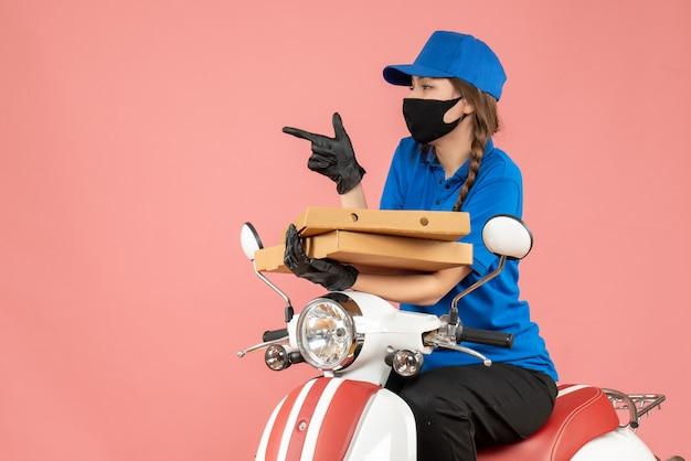 Vista frontale di una giovane curiosa corriere femminile che indossa maschera medica e guanti seduto su uno scooter che consegna ordini su sfondo color pesca pastello