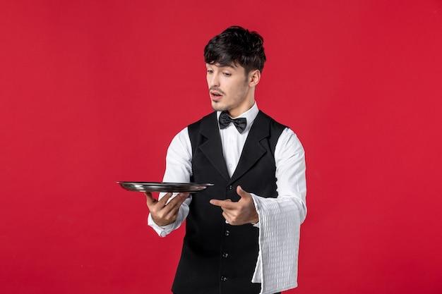 Vista frontale di un giovane cameriere maschio curioso in uniforme con papillon sul collo che tiene il vassoio e asciugamano sulla parete rossa