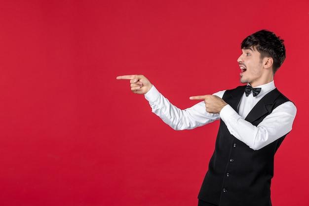Vista frontale di un giovane cameriere maschio curioso in uniforme con papillon sul collo e rivolto verso l'alto sul lato destro con entrambe le mani sul muro rosso