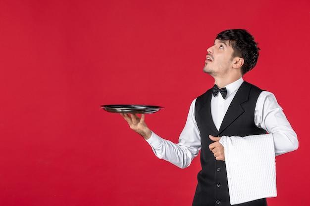 Vista frontale di un giovane cameriere curioso in uniforme con papillon sul collo che tiene vassoio e asciugamano che guarda in alto sul muro rosso