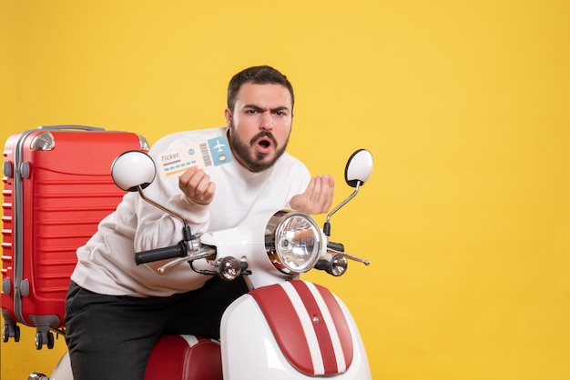 Front view of young curious travelling man sitting on motorcycle with suitcase on it holding ticket on isolated yellow background
