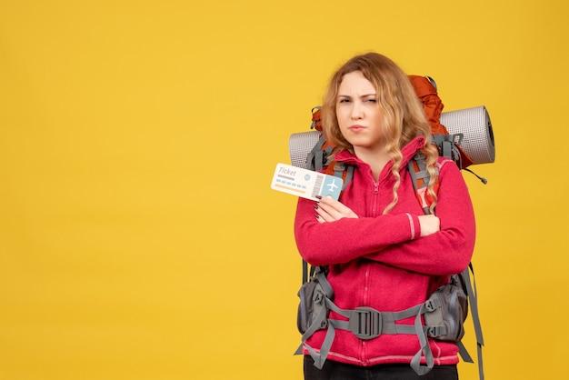 Vista frontale della giovane ragazza di viaggio insoddisfatta nel biglietto della holding della maschera medica