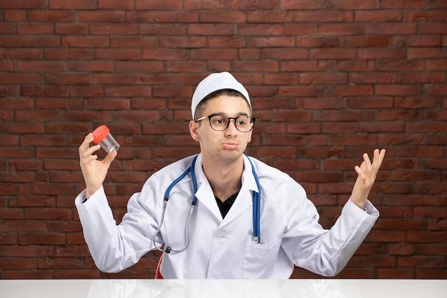 빈 작은 플라스 크를 들고 흰색 의료 소송에서 전면보기 젊은 의사