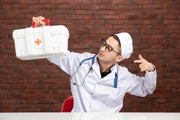 응급 처치 키트와 함께 흰색 의료 소송에서 전면보기 젊은 의사