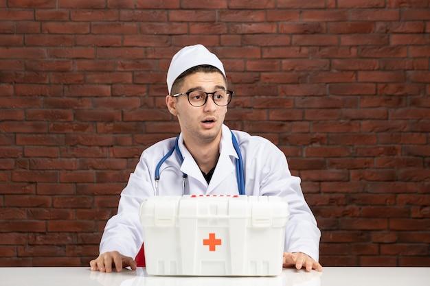 Вид спереди молодой врач в белом медицинском костюме с аптечкой