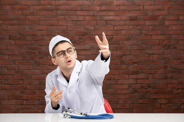 Вид спереди молодой врач в белом медицинском костюме