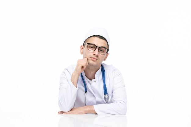 Front view young doctor in medical suit sitting behind desk