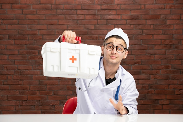 Front view young doctor in white medical suit with first aid kit