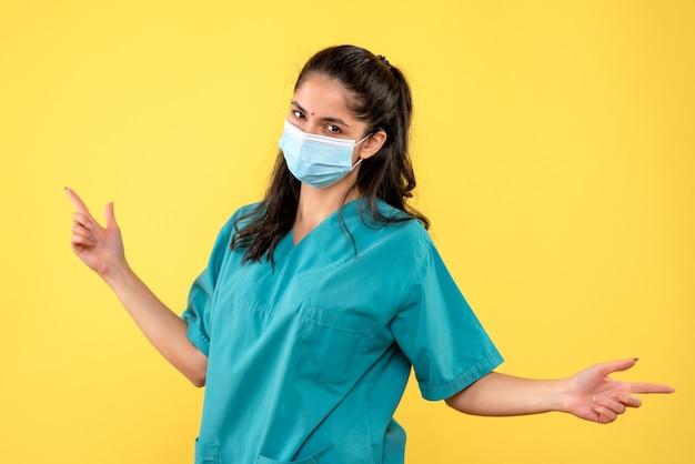Vista frontale del giovane medico con maschera aprendo le mani in piedi sul muro giallo