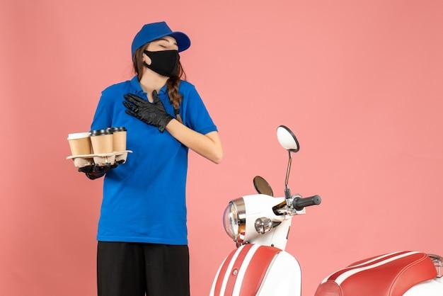 Vista frontale della giovane ragazza corriere sognante che indossa guanti con maschera medica in piedi accanto alla moto con in mano piccole torte di caffè su sfondo color pesca pastello