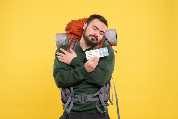 Vista frontale del giovane ragazzo in viaggio da sogno con lo zaino e che mostra il biglietto su sfondo giallo