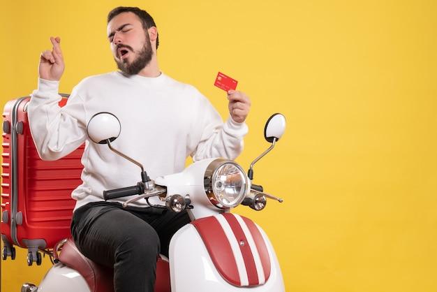 Vista frontale del giovane uomo in viaggio sognante seduto su una moto con la valigia sopra che tiene il dito incrociato della carta di credito su sfondo giallo isolato